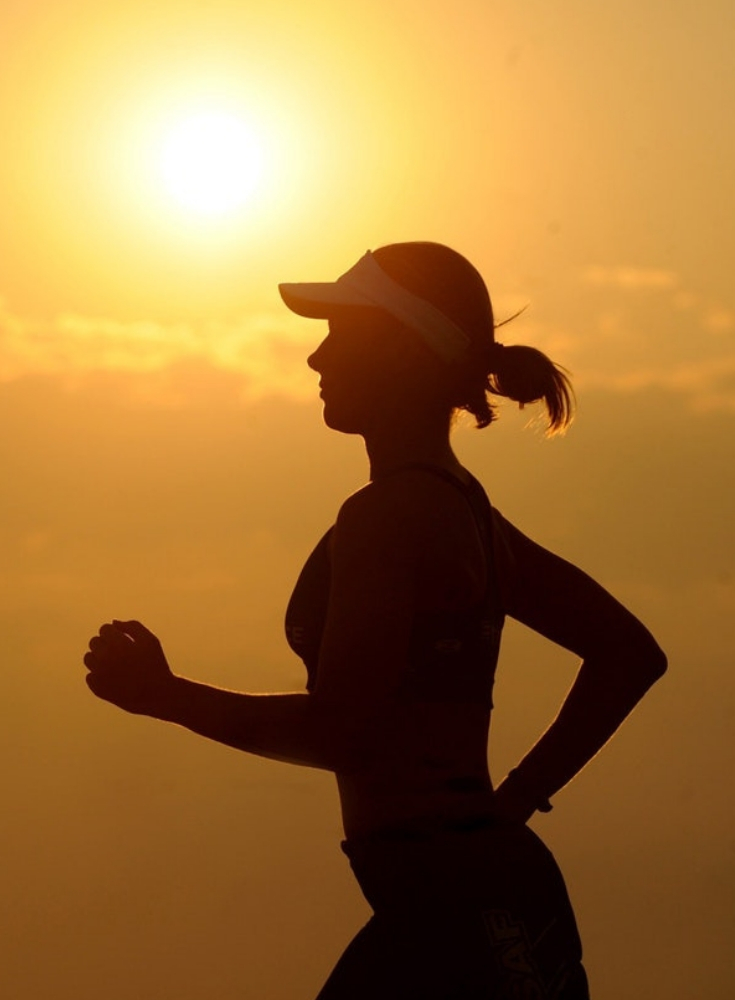 girl running with sunrise behind her